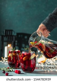 Female hand pours winter sangria in glasses with fruit slice, cranberry and rosemary. Dark christmas holiday background with candle, decoration lighting chain. Copy space for text or design. Vertical