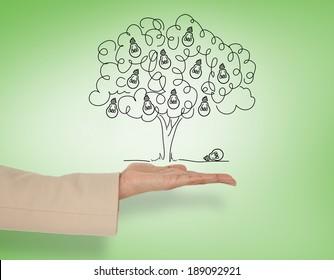 Female hand presenting light bulb tree against green vignette