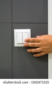 Female hand presses an electric switch.