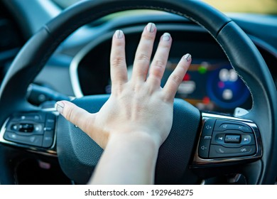 female hand presses the horn on the steering wheel of a modern car. no face