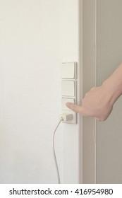 Female hand pressing white  electric socket