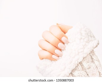 Female hand with professional manicure of natural pastel color and art design wearing in wool sweater.