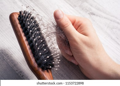 Female Hand Pulling Bunch Of Hair Out Of Brush - Alopecia Hair Loss Concept