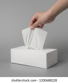 female hand pulling white facial tissue on grey background for print design and mock up