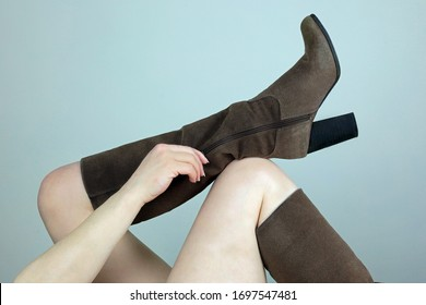 A Female Hand Pulling Up A Zip On A Brown Suede Knee High Boot.