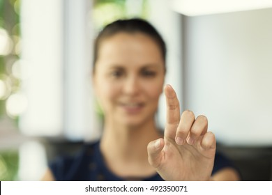 Female hand pushing a digital screen at office background. focus on finger