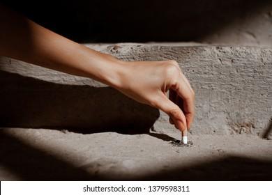 Female hand put out a cigarette on a concrete floor