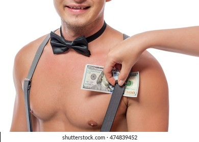 female hand puts dollars under the strap suspenders strippers