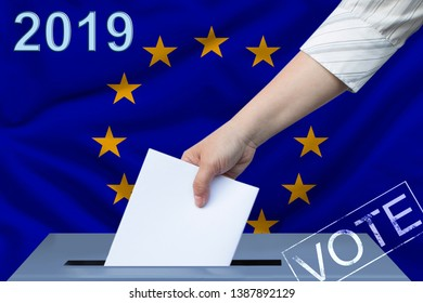 Female hand puts down a white sheet of paper with a mark as a symbol of a ballot paper against the background of the flag of the European Union, the symbol of a parliamentary elections.