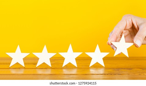 A female hand puts the fifth wooden star on a table