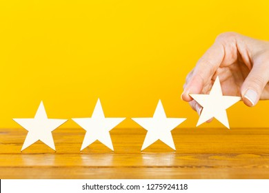 A female hand puts the fourth wooden star on a table
