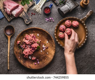 Female hand puts meat ball in frying pan. Preparation on kitchen table with meat, force meat , meat grinder and spoon, top view. Cooking,recipes and eating concept