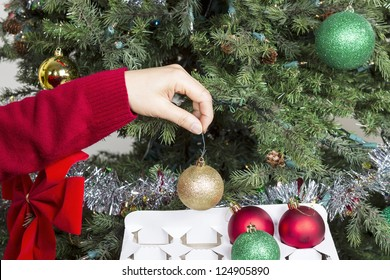 Female hand putting away Golden holiday ornament into white card board box to end the season