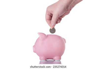 Female Hand Putting a Coin into a Piggy Bank Isolated on a White Background.