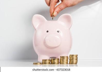 Mano de mujer metiendo moneda en un banco de cerdo aislado de fondo blanco