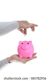 Female hand putting a coin into piggy bank isolated on white background  with clipping path