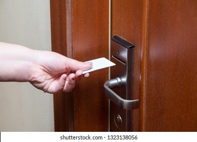 Female hand putting key card switch in to open hotel room door. Holding magnetic card for door access control scanning key card to lock and unlock door
