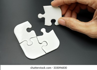 Female hand putting a missing piece and solving white jigsaw puzzle placed on top of colour background - complete. business, challenge, solution, smart and strategy concept