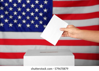 Female hand putting voting ballot into the box  on American flag background