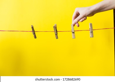 female hand reaches for a clothespin. four clothespins hanging on a red clothesline. Extremely high quality yellow background. laundry. washing and drying clothes