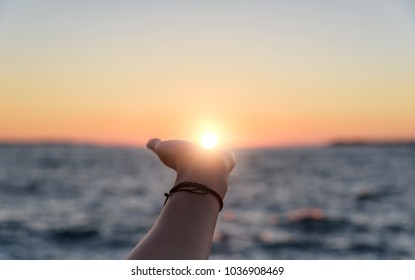 Female hand reaches for the sun at sunset against the background of the sea.