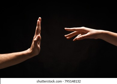 Female hand reaching male, man making stop sign at black isolated background. Relationships problems, family issues, copy space