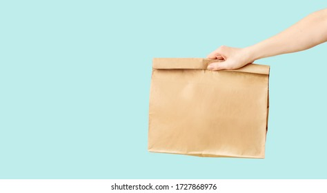Female hand receiving brown clear empty blank paper bag for food delivery on blue background with copy space. Packaging template mock up fast food.