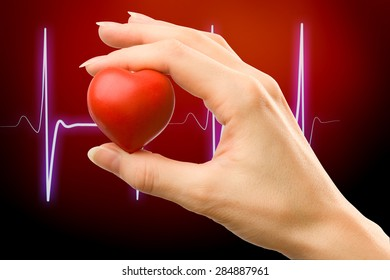Female hand with red heart carefully holding