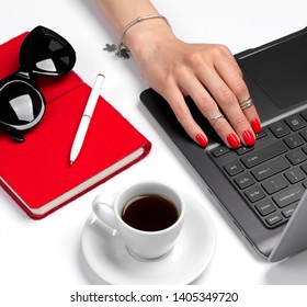 Female hand with red manicure on laptop. Feminine office table with laptop, notebook, pen, coffee and sunglasses.