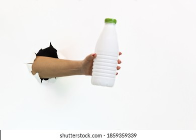 A female hand with a red manicure in a torn hole on a white background holds a white plastic bottle with a green cap. Hand through torn white paper