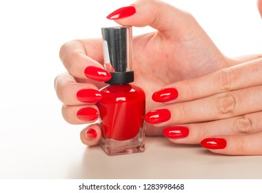 Female hand with red nail polish bottle