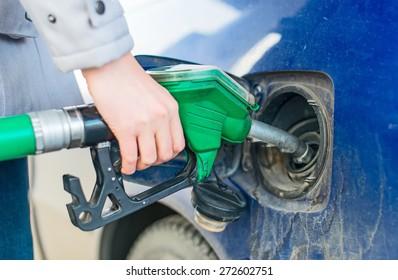 Female hand refueling dirty blue car.