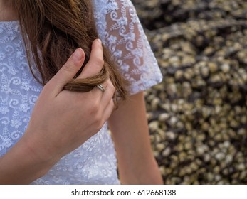 A female hand and a ring in a white blouse holds her hair against the rocks