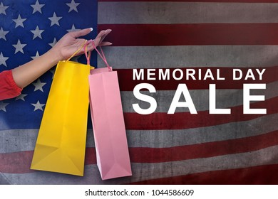 Female hand with shopping bag on memorial day sale with american flag background