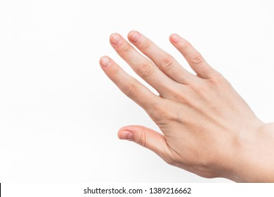 female hand with short nails and neat manicure without varnish on a white background, arthrosis of the joints, normal skin