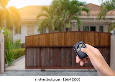 Female hand showing and using remote control to open or close the automatic wooden gate with home blurred background. Security and save time concept.