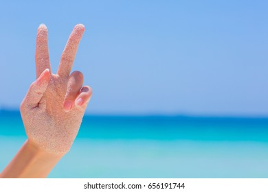 Female hand showing victory sign on blue sea background