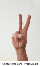 Female hand shows two fingers on a white background