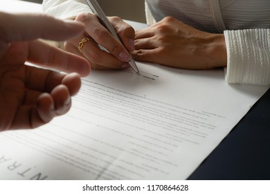 Female hand signing contract.