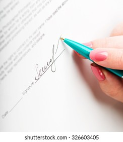 female hand signing a contract.