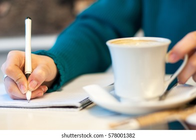 female hand signing in notebook and drinking coffee, on bright background