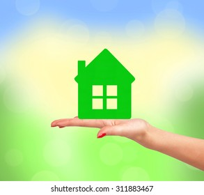 Female hand with small model of house over bright nature background