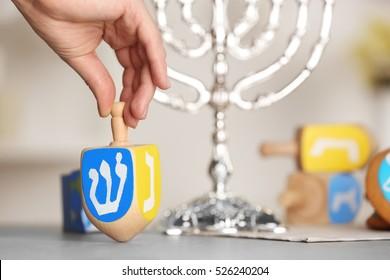 Female hand spinning wooden dreidel for Hanukkah on light table