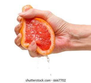 The female hand squeezes out juice from a ripe grapefruit. Isolation on white.