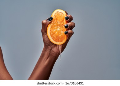 Female hand squeezing orange isolated on grey. Copy space