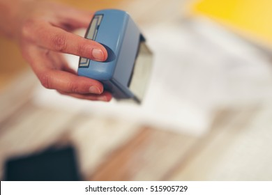 Female hand stamping document, working at office