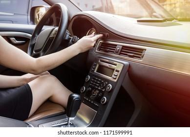 Female hand with start key inside car