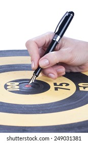female hand sticks a Fountain pen in the target center dartboard over white
