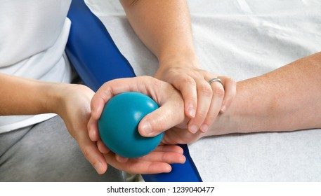 Female hand stimulation using exercise blue ball with help from physiotherapist