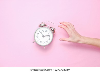 Female hand takes alarm clock on pink background. Top view. Time to wake up. Minimalism